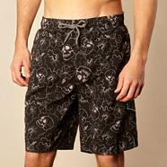 Black skull patterned board shorts