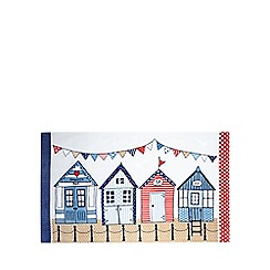 At home with Ashley Thomas - Navy beach huts beach towel