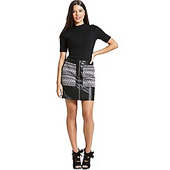 Girls On Film - A black faux leather and aztec print skirt